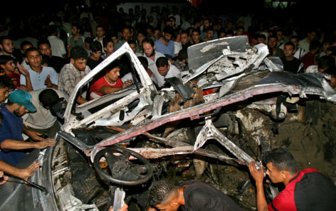 Palestinians surround a destroyed car after it was hit by a missile in Gaza