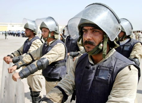A group of Iraqi policemen in full riot gears stand in formation during anti riot training in Basra