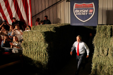 U.S. President George W. Bush walks between hay bales enters a campaign event in Ohio