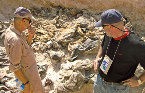 Archaeologist Trimble and lawyer Kehoe view a mass grave site being excavated in Hatra