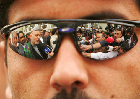 Image: Afghan President Karzai is seen reflected in the sunglasses of a security guard.