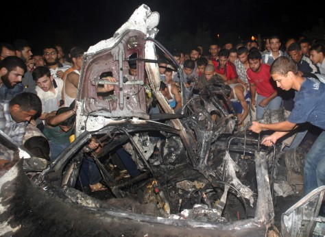 IMAGE: Palestinians gather around the wreckage of the car in which Adnan al-Ghoul was killed Thursday.