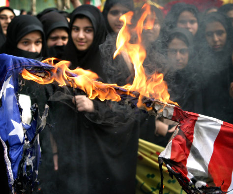 Iranian women stand behind a burning American flag in Tehran