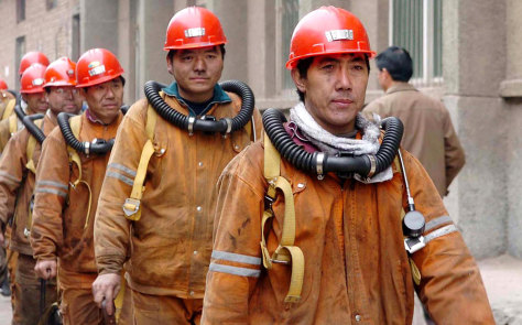 Chinese rescuers emerge from the underground tunnel in Chenjiashan