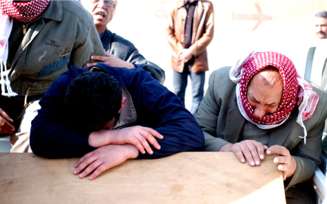 Image: Relatives cry over coffin of assassinated Iraqi official.