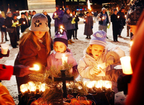 Image: Woman, children light candles.