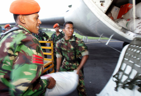 Indonesian soldiers load sacks of food