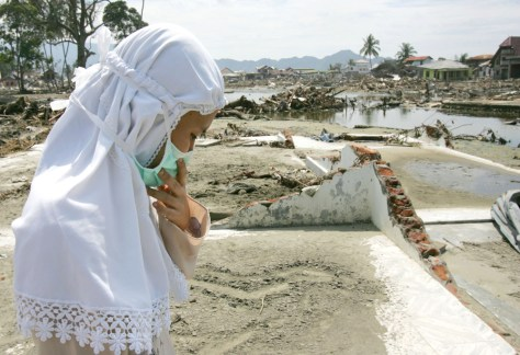 Image: Woman stands on the remains of her Banda Aceh home.