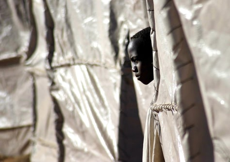 Image: Refugee boy looks out of plastic tent.