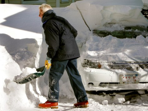 MAN DIGS CAR OUT OF SNOW