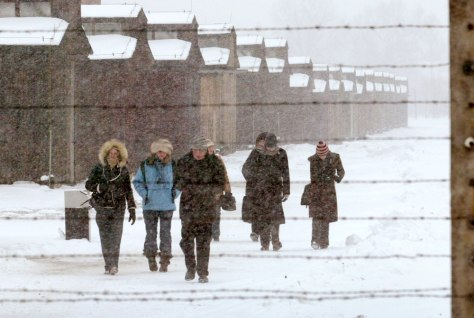 Visitors walk inside former death camp Auschwitz II-Birkenau during a heavy snow storm in Oswiecim