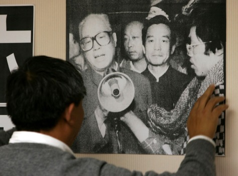 Worker puts up poster of late Zhao Ziyang in Hong Kong