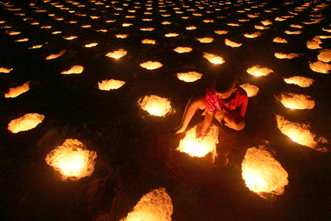 Image: Child lights candles on a beach.