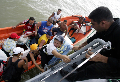 Venezuelans climb aboard a navy ship during an evacuation after torrential rains in Vargas state