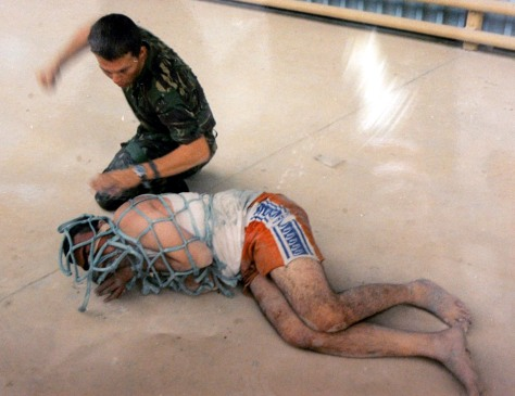 Image: British soldier abuses an Iraqi prisoner.