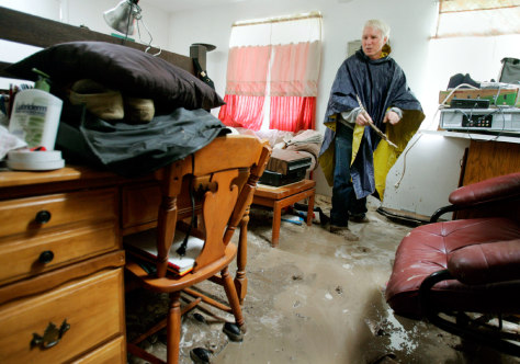 Don Kuhli collects his belongings after a mud slide filled his apartment.