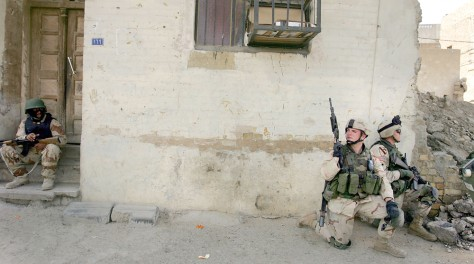 Image: U.S. soldiers, right, take position along with an Iraqi soldier, left.