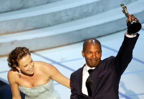 Jamie Foxx accepts his best actor award from actress Charlize Theron at the 77th annual Academy Awards