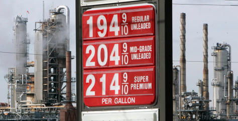 Fuel prices are displayed at a gas station across the street from a Citgo refinery