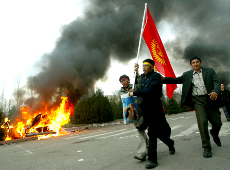Kyrgyz opposition protesters walk past a burning car in Bishkek