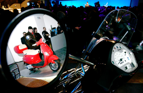 The Vespa LX, the new model is reflected on the rear view mirror of another one at a presentation ceremony in Rome