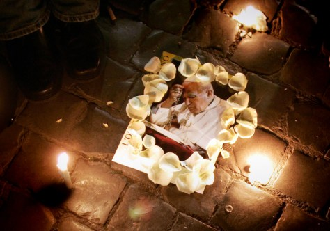 A poster of Pope John Paul II lays next to candles in Saint Peter's Square at the Vatican