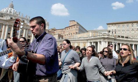 Image: Catholics hold hands and pray for the Pope in St. Peter's Square.