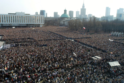 Polish faithful pray during a special mass for the late Pope John Paul II at Pilsudski Square in Warsaw