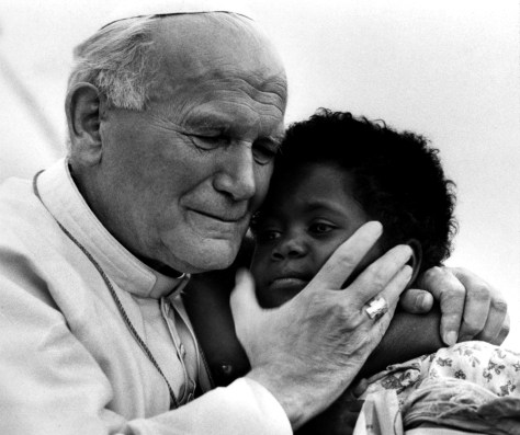 A file photograph of Pope John Paul II hugs three-year-old Monik and her one-year-old sister Zin in Madagascar