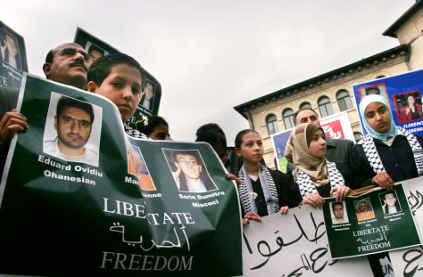 Children from the Arab community in Romania hold banners during a rally in Bucharest for kidnapped journalists in Iraq