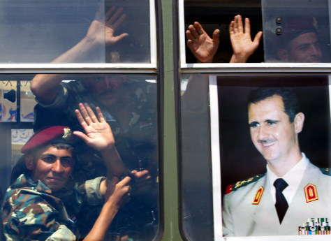 Image: Syrian soldiers wave behind a poster of their president.