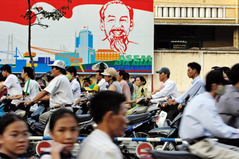 Image: Vietnamese commuters pass a portrait of Ho Chi Minh.