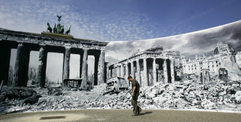 A man walks in front of a large photographic print of the destroyed Pariser Platz after World War Two in Berlin