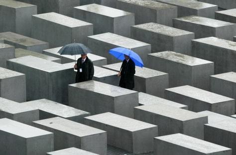 People walk between the concrete steles