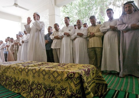 Image: Men pray around Iraqi official's coffin.