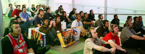 Group of guys watch Xbox 360 presentation