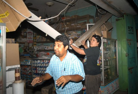 Image: Chilean residents fix up their shop after an earthquake.