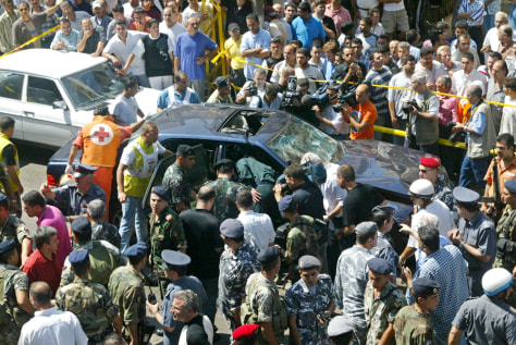 Image: Crowd surrounds car damaged by bomb blast.