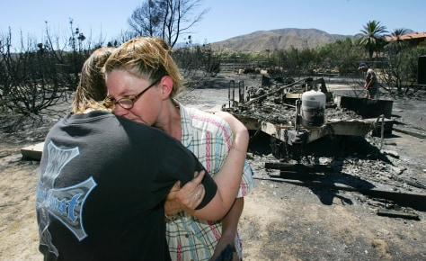 Image: Mother, daughter hug next to burned down trailor.