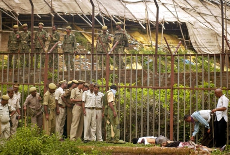 Indian soldiers inspect unidentified dead gunmen on a religious site in Ayodhya
