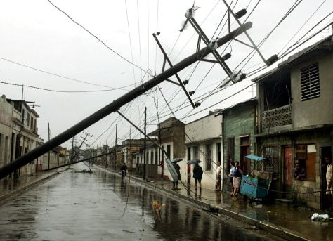 Residents look at knocked-down power lines after Hurricane Dennis in Cuba