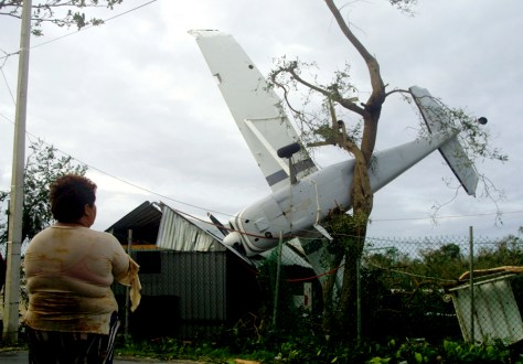 Mexican woman looks at aircraft which was flipped onto tree by Hurricane Emily's in Playa del Carmen, Mexico