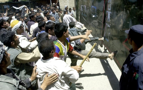Afghan protesters kick towards a gate du