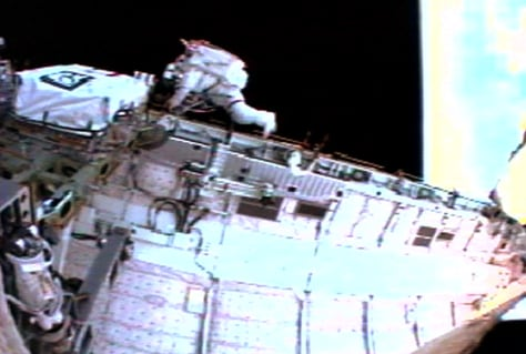 Astronaut Soichi Noguchi makes his way along the sill of the payload bay
