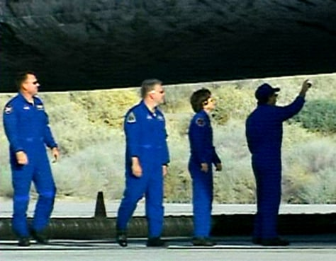 Discovery crew members inspect the underside of the space shuttle