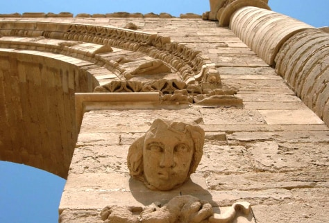 The face of a woman stares down at visitors in the Hatra ruins