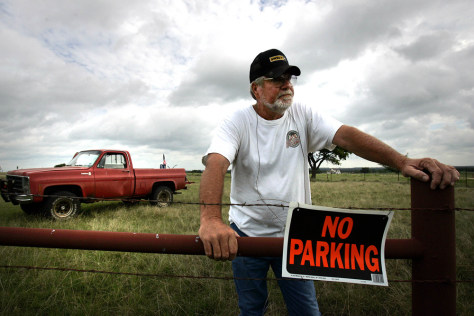 Image: Larry Mattlage look out at protesters from his ranch in Crawford, Texas.