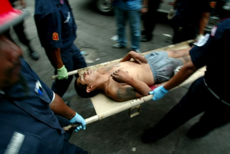 Volunteer firemen remove an injured gang member