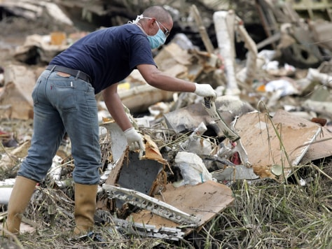 A rescue worker searches among the wreckage of West Caribbean Airways MD-82 aircraft in Machiques