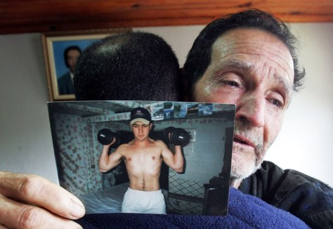 Image: Father holds photo of slain Jean Charles de Menezes.